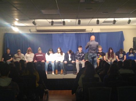 Sailesh standing in front of a row of hypnotized students.